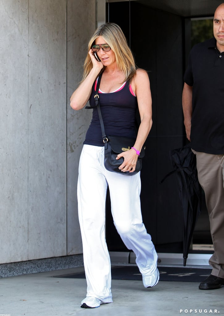 Jennifer Aniston chatted on the phone post-workout in LA yesterday. She was dressed down in white fitness pants, tennis shoes, and a tight tank after also hitting the gym in casual gear last week. Her hard work paid off over the weekend when she made an appearance in a sexy dress at the MTV Movie Awards. Jennifer wore a sexy black leather look to accept her best onscreen dirtbag golden popcorn for Horrible Bosses at the show. She's since shared another funny role with fans, having participated in a spoof of The Bachelor. Jennifer wears a bear costume in Burning Love, a Yahoo! web series that debuted yesterday and also features Malin Akerman and Kristen Bell.