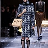 We think Kate's coat-dress collection could use a fun print, like the navy, retro design on this double-breasted number Miuccia Prada sent down the runway.