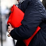 An oversize red leather clutch popped against a black coat.