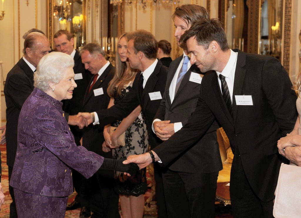 Hugh Jackman arrived at London's Buckingham Palace tonight dressed in a suit and tie for a face-to-face meet and greet with the Queen of England. Elle Macpherson joined Hugh and other popular Australians at the reception hosted by her majesty.  Hugh was beaming ear to ear all night long, and it may be that he's still basking in the success of Real Steel's first-place finish at the box office over the weekend. His robocentric family flick took home first place with $27.3 million, beating out George Clooney and Ryan Gosling's political drama The Ides of March. In addition to the film's success, Hugh also celebrated his 43rd birthday yesterday. The date proved to be twice as meaningful this year as Hugh also launched a new company, Laughing Man, on the date. The philanthropic brand sells fair trade coffee, tea, chocolates, and gear and will donate 100 percent of its profits to charity.