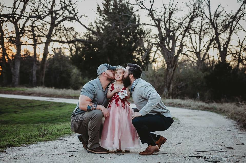 """Willow Grace is one lucky girl — she has three loving parents: a mom and two dads. In a handful of photos taken by her mom, Sarah of Willie + Rose Photography, Willow can be seen with her two dads — her biological father, David (right), and her """"bonus dad,"""" Sarah's fiancé, Dylan (left) — and you can just tell from the photos how much love these two men have for their little girl. """"I want him to feel like he's here when he's not."""" David lives in New Mexico while Sarah and Dylan live in Texas with 5-year-old Willow and their 2-year-old daughter, Tatum, but even with a 14-hour drive between them all, that doesn't stop David from being fully involved in his daughter's life. """"Coparenting with Dylan and David has been pretty easy because we keep our communication super open,"""" Sarah told POPSUGAR. """"We FaceTime almost every day with David and we send texts and pictures and videos of Willow to keep him in the loop constantly and so that he can watch her grow up when he's not physically there. I think that's been important to all of us — communication is the key to making this work. I let David know everything. I want him to feel like he's here when he's not.""""      Related:                                                                                                           How These 5 Adults Make Coparenting Their 2 Children Look Effortless               In addition to communicating while they're all apart, Sarah says David comes up to visit as much as his job allows him to, and they handle holidays however it makes sense for them so it works for all parties. And it's not just Willow who gets the benefit of two dads when David's around — Tatum loves him, too, and even calls him Dad. """"He walked through the door the other day and brought both girls doughnuts, and she ran down the hall screaming, 'Dad!'"""" Sarah said. Dylan added: """"Anytime he leaves — even if he's just going to the store while he's here — when he comes back she reacts like it's me coming home from work. It's """