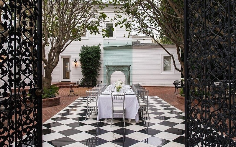 The checkerboard floor of this outdoor dining patio is made from black-and-white marble.