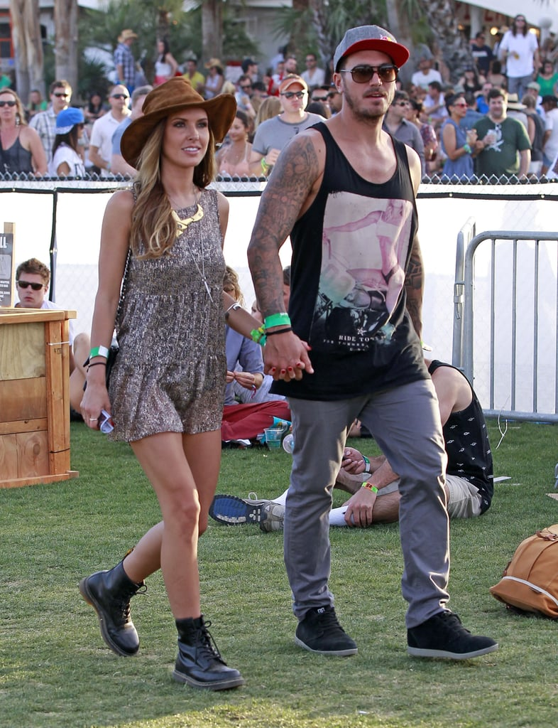 Audrina Patridge and her man hit up Coachella, with Audrina rocking a printed minidress, black combat boots, a brown hat, and a bevy of gold jewels.