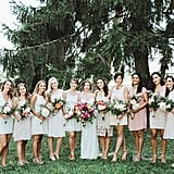 This big group of bridesmaids seamlessly coordinated in pinks, creams, whites, and peaches.