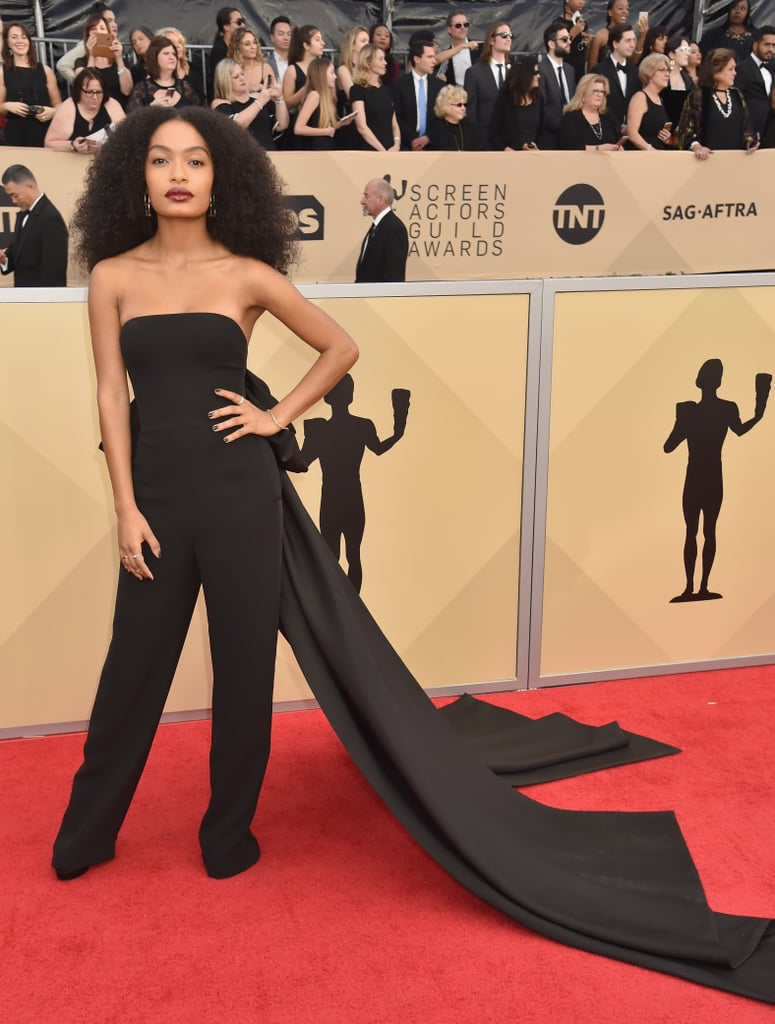 Yara Shahidi arrived at the 2018 Screen Actors Guild Awards in an elegant hybrid ensemble. Instead of choosing between a classic gown or daring jumpsuit, the 17-year-old Grown-ish star opted for a little bit of both by wearing a strapless tuxedo jumpsuit with a dramatic train. Yara kept the rest of her look simple, opting to go without a clutch and wearing black pumps and minimal gold jewelry. See her multifaceted (and multipurpose!) look ahead.