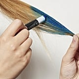 Firmly grasping your left ponytail by its tip, color your hair from the halfway point down with the blue chalk. Blend the line of demarcation with your fingers to create an ombré effect.