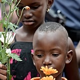 Two kids held up flowers while attending the public memorial at Nelson Mandela's Houghton home.
