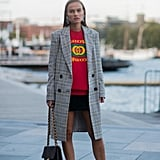 Put on your favorite black miniskirt with a sweatshirt and trainer sneakers, then throw on your long plaid double-breasted coat.