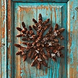 This snow-dusted wreath looks right at home with the turquoise and natural wood tones of this worn door.  Source