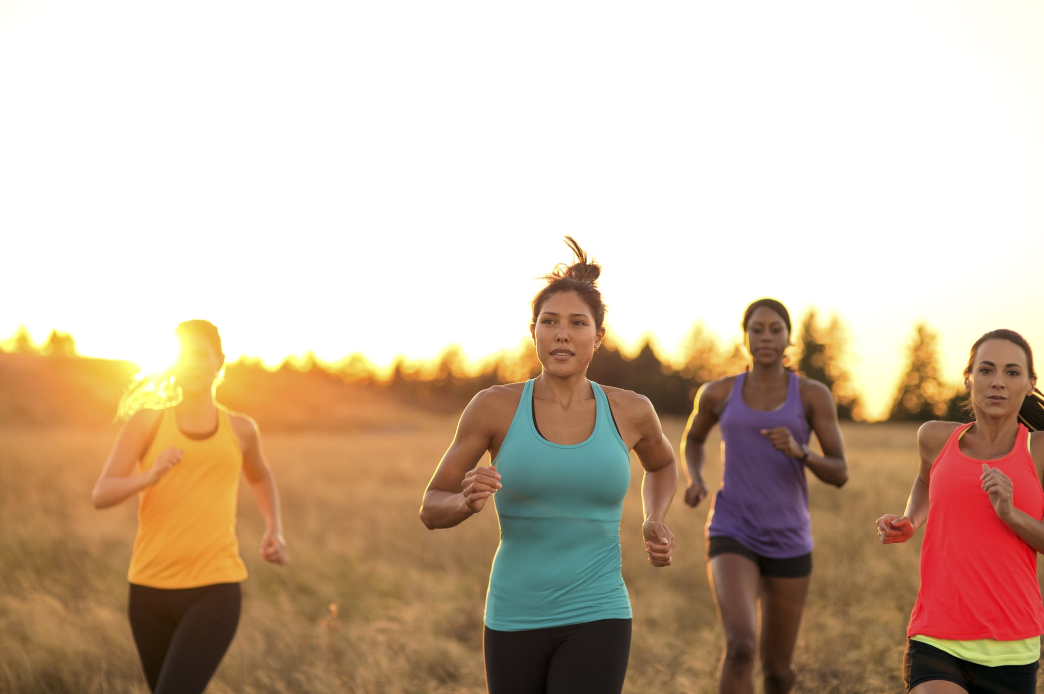 Group of diverse adult females trail running as the sun sets behind them