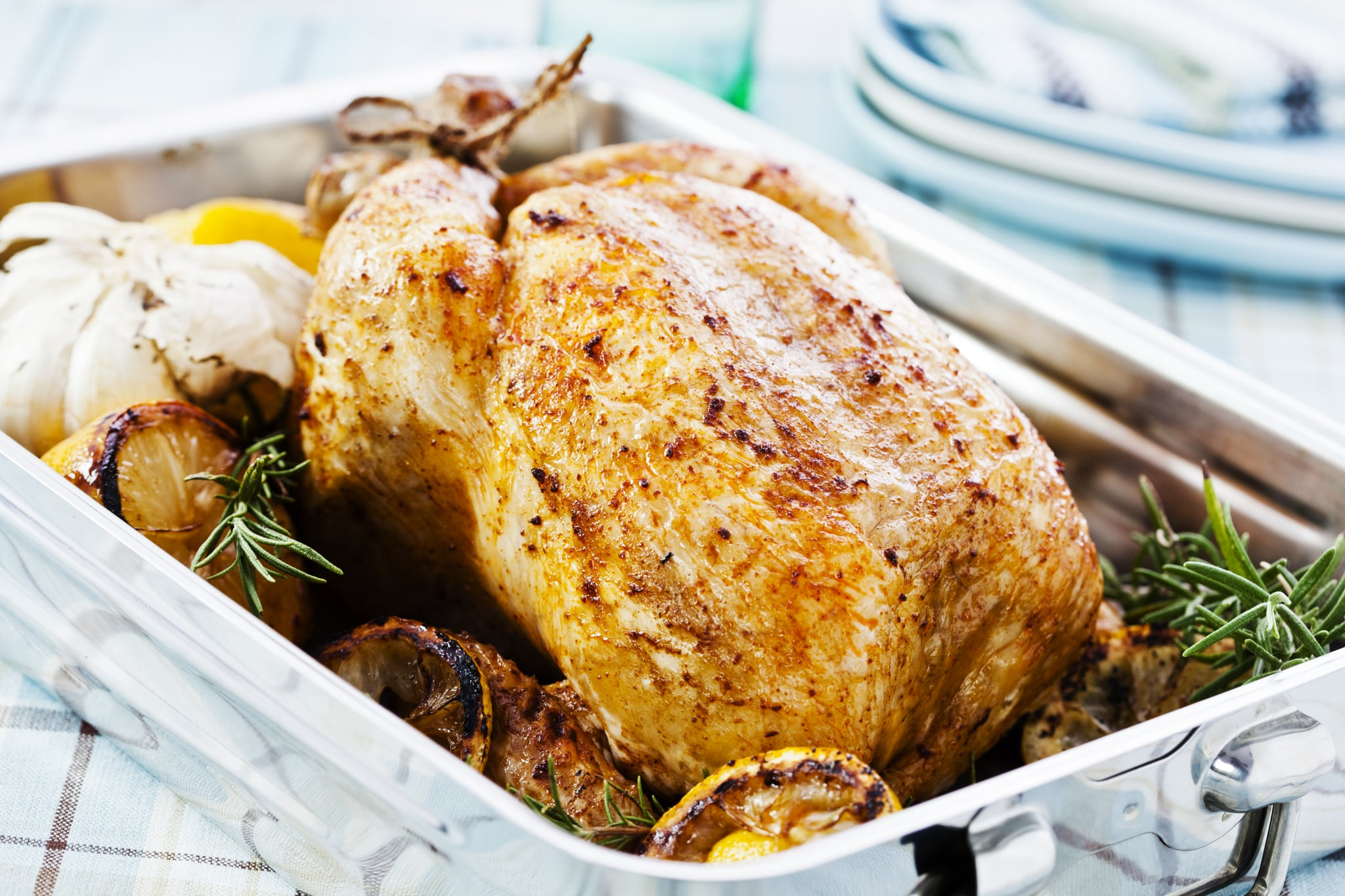Roasted chicken in a pan with lemon, garlic and rosemary