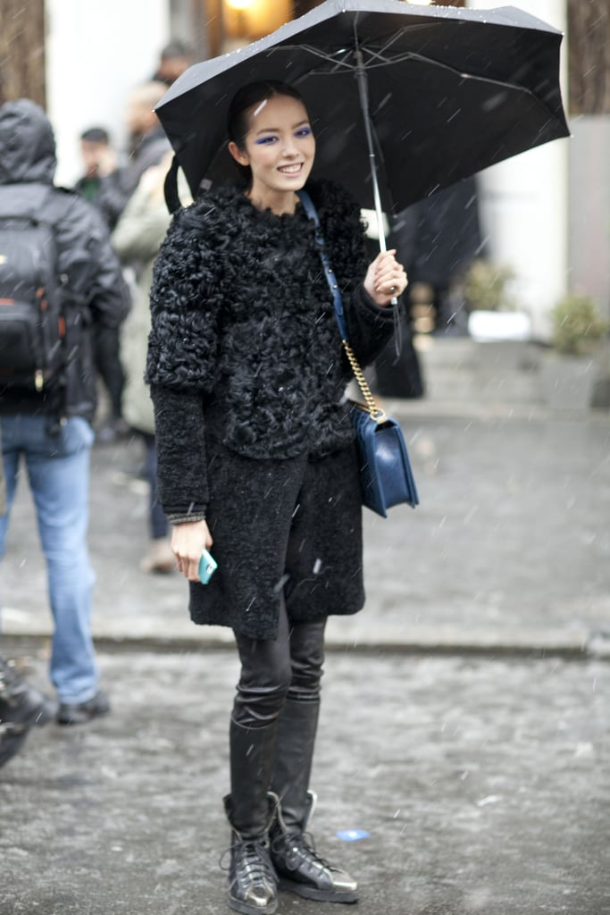 Battling the snow with umbrella in hand, and the most luxurious of outerwear.