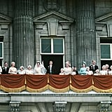 The royal family — including Queen Elizabeth II in bright blue on the right — wave from the balcony of Buckingham Palace.