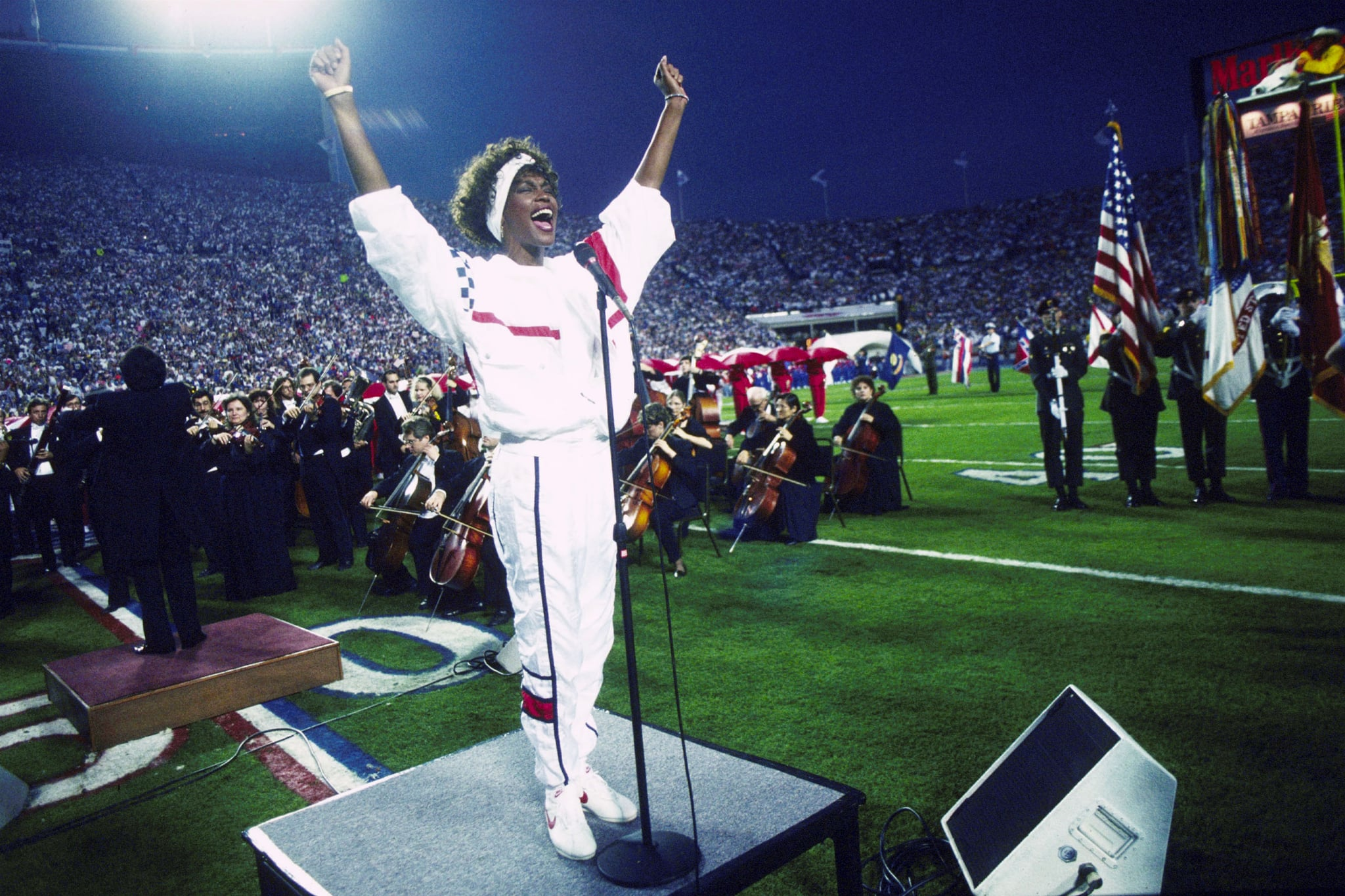 TAMPA, FL - JANUARY 27:  Whitney Houston sings the National Anthem during the pregame show at Super Bowl XXV while tens of thousands of football fans wave tiny American flags in an incredible outburst of patriotism during the Persian Gulf War on 01/27/1991.  (Photo by Michael Zagaris/Getty Images)