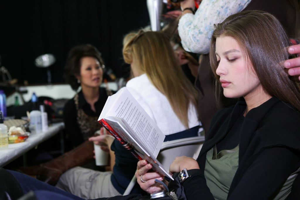 While getting her hair done, this model read backstage at Richard Chai's Fall 2005 show.