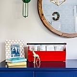 A rustic mirror and vintage light fixtures complete the look, while diapering supplies are creatively displayed in a toolbox.
