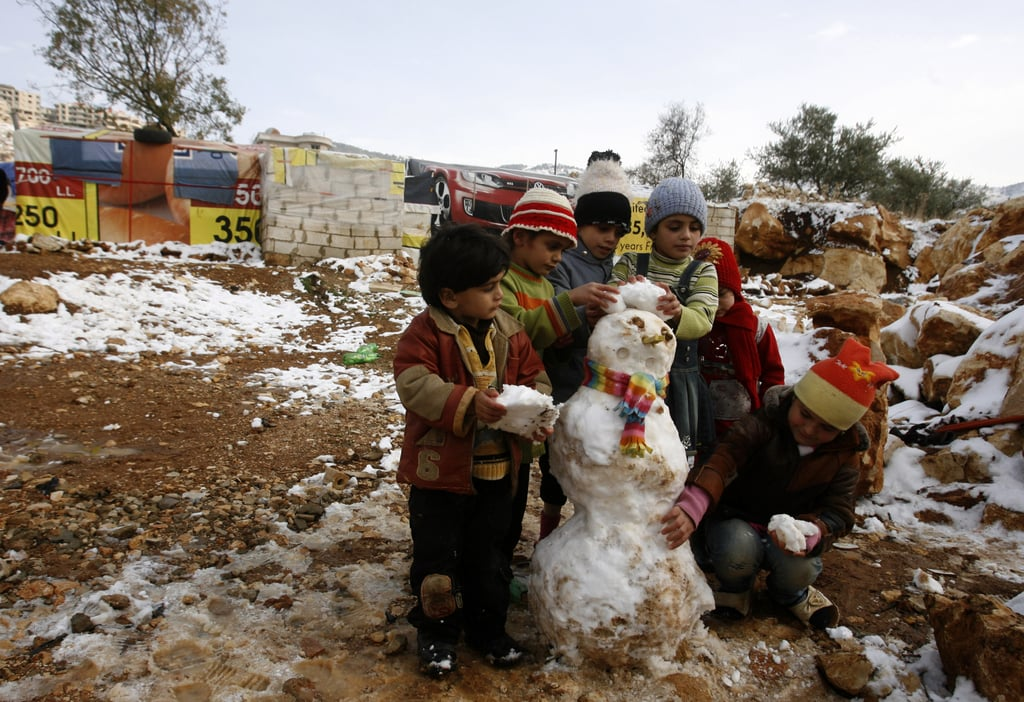 Young Syrian refugees built a small snowman in a makeshift refugee camp in the Bekaa Valley.