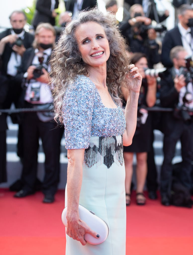 """Life amid a pandemic changed many people's beauty routines, including Andie MacDowell's. The actress (known for her iconic curls) used the past few months to experiment with her naturally grey roots. This past week, MacDowell brought her salt-and-pepper style to the red carpet for the first time at the Cannes Film Festival. She previously revealed her kids encouraged her to embrace the colour, and we're thrilled they did.  Earlier this year, MacDowell gave a little backstory on her hair evolution during a Drew Barrymore Show interview. When she stopped colouring her hair, her daughters, Margaret and Rainey Qualley, told her she looked """"badass"""" with silver streaks at her roots. Their excitement gave MacDowell confidence to become a """"silver fox"""" at age 63. """"It's not that I'm letting myself go, I don't think of it that way,"""" she emphasised. Instead, she's reveling in a new experience for the time being. """"I don't know what's going to happen in five years, I may colour my hair again, but I'm enjoying it right now."""" See more photos of MacDowell's glamorous grey hair at Cannes in the photos ahead.       Related:                                                                                                           These Are Most Stunning Red Carpet Gowns Straight From the Cannes Film Festival"""
