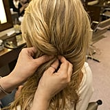 Pull your hair over to the side you want your braid to rest. Then, loosely twist a side section of hair behind your ear and pin in place. Later you'll join this twist with the braid you're about to create.