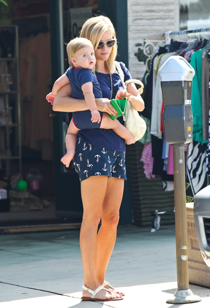 Reese Witherspoon held on to her son as she fed the parking meter.