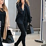 Moss spotted at JFK Airport in her signature black skinny jeans, and black buttoned Oxford blouse.