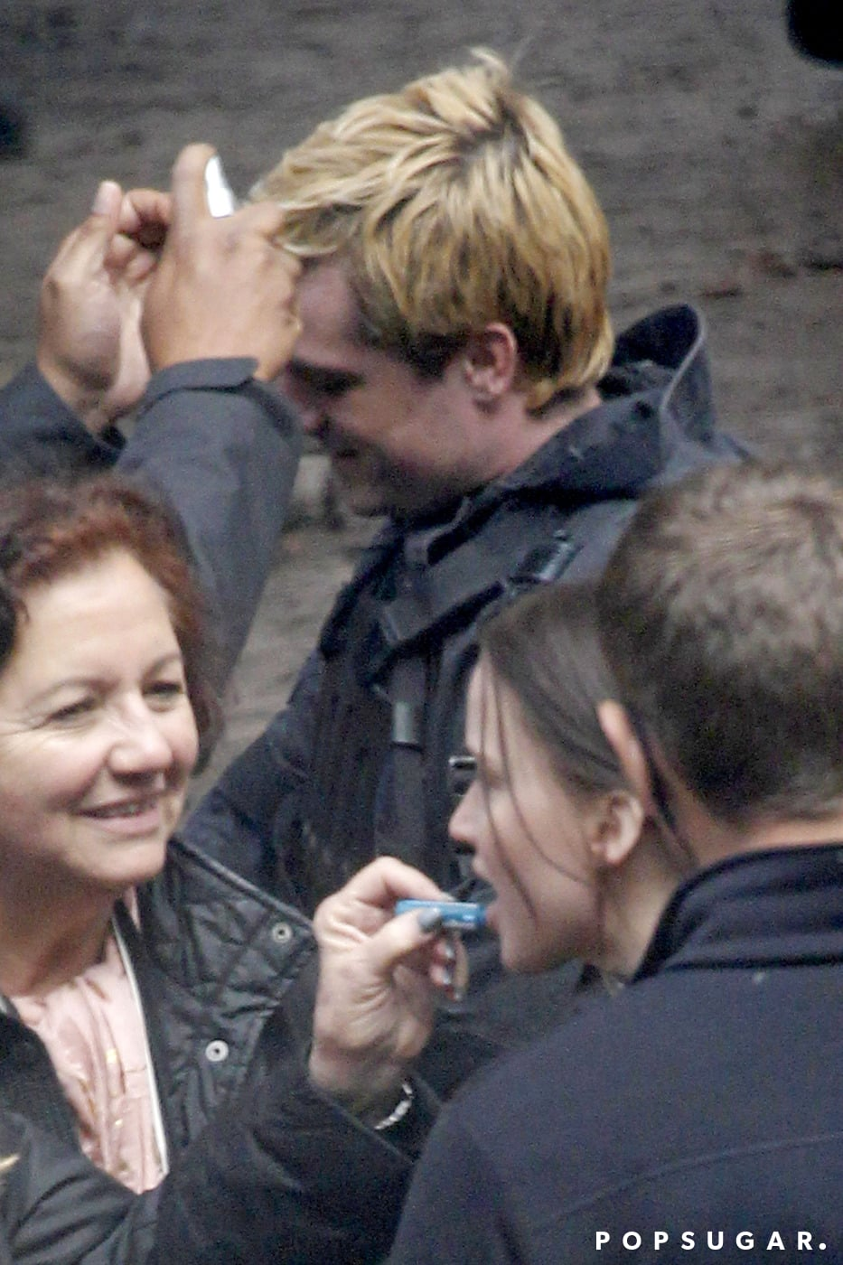 A stylist adjusted Hutcherson's hair during a break.