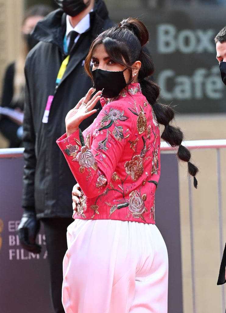 Priyanka Chopra decided that the 2021 BAFTA Awards was the perfect time to try out not one, but two of the biggest beauty trends right now: a stylish black tip french manicure and an incredible bubble braid.  To achieve the look, hairstylist Luke Pluck Rose sprayed Anomaly Dry Shampoo (Chopra Jonas's new hair-care brand) throughout the tail, before creating the bubble effect by securing seven small, brunette-hued hair bands approximately two inches apart and tightening to form the small bubbles. Finally, Pluck Rose softened the look by adding slight waves in Chopra Jonas's bangs.  Our favorite thing about this particular hairstyle is that it's relatively easy to re-create at home. Now, we can't promise it'll look as good as Chopra Jonas's — I mean, we're not professionals after all, but we can try, right? Our top tip is to match bands to your hair color and give your hair a generous spritz of volumizing spray.  Check out more photos of Chopra Jonas's bubble braid at the BAFTA Awards ahead.