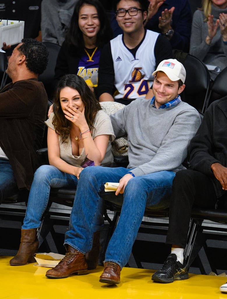 """Mila Kunis and Ashton Kutcher packed on the PDA during a Friday date night at a Lakers game in LA. The pair sat courtside in their first public joint appearance since Mila gave birth to daughter Wyatt in October. Ashton and Mila shared several kisses throughout the game, with Mila getting in a giggly mood after one particular smooch. The couple also posed for selfies with fans and shared a funny exchange with Kobe Bryant while he was on the court. The actress also gave a glimpse of a cute memento for her daughter — a silver necklace she wore that featured a """"W"""" etched into a silver circle.  The couple has slowly been getting back into public life since welcoming their first daughter two months ago. Mila recently gave her first postbaby interview on the Late Show With David Letterman, explaining that Wyatt's possibly rebellious teenage years will be """"daddy's problem."""" Meanwhile, Ashton appeared on The Ellen DeGeneres Show earlier this month where he revealed that he and Mila have yet to get a nanny because they want to spend as much time with their little one as possible."""