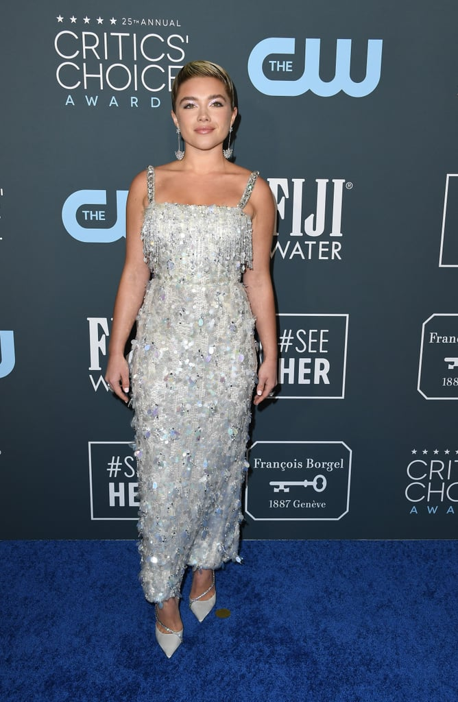 Florence Pugh's iridescent Prada gown on the Critics' Choice Awards red carpet on Sunday could have out-glimmered a chandelier. The stunning silver dress was practically dripping with sequins and rhinestones, all held up by embellished straps that make her shoulders look so expensive — and they might be our new favorite trend.  Pugh paired the glittery silver gown with matching drop earrings and a pair of Jimmy Choo Talika Suede Pumps ($995) featuring a cross-foot chain bedazzled with rhinestones — glamorous. Take a closer look at the actress's brilliant gown ahead, and keep scrolling to see how Pugh makes all that sequins shimmer on the red carpet.