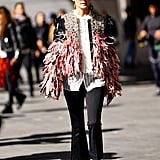 During the Paris shows, Olivia turned the sidewalk into a runway with this feather-trimmed and embellished jacket to top black pants and bow-adorned flats.