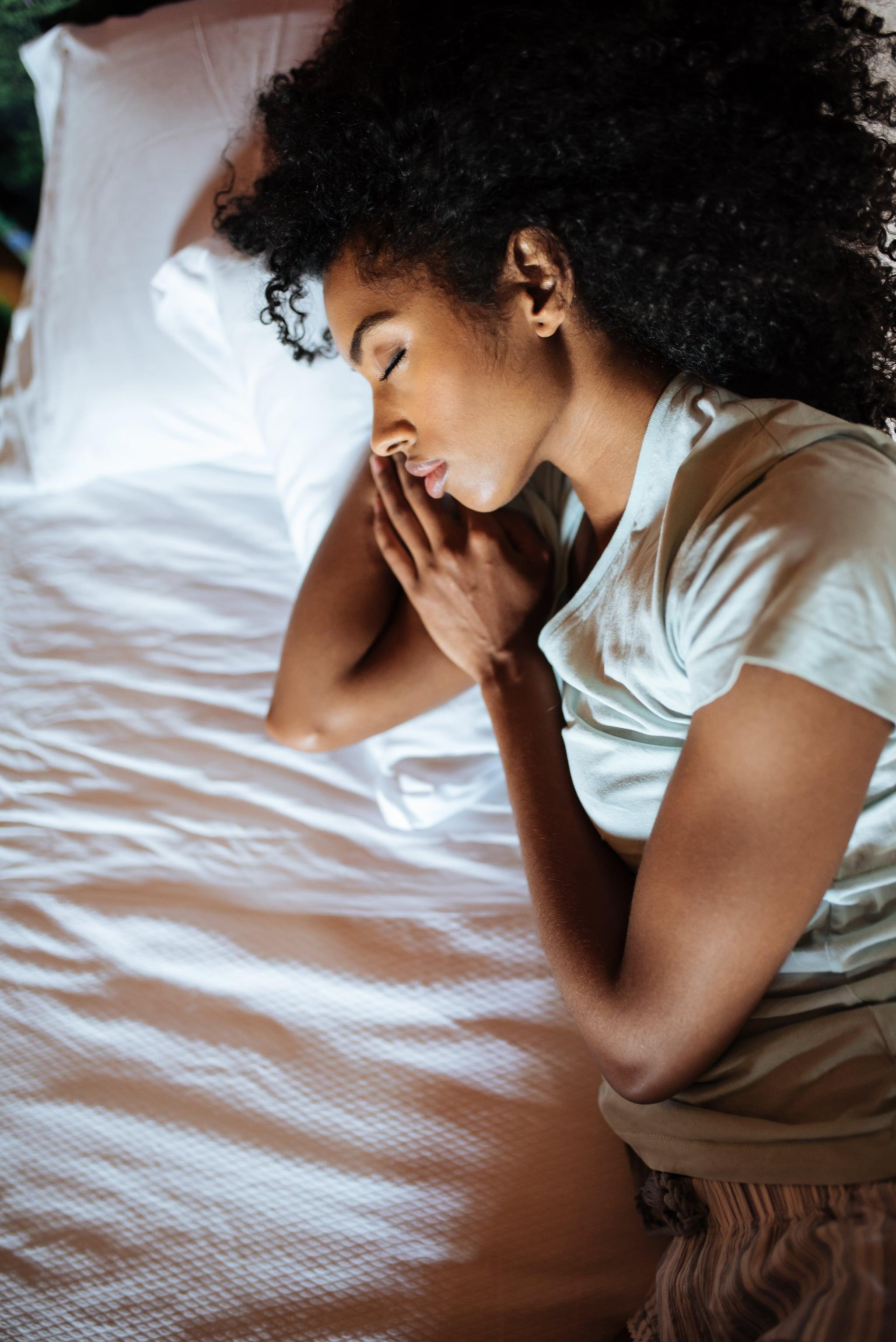 Beautiful black woman lying down in bed sleeping