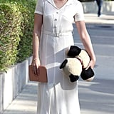 Kristen took a stroll on set in a feminine white dress, which she accessorized with T-strap heels, a tan clutch, and a stuffed panda.
