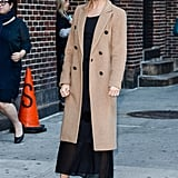She Knows She'll Look Just as Spiffy When She Covers Her LBD With a Camel Coat