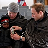 Harry and Will helped a little boy put gloves on during a visit to a child education center in Lesotho in June 2010.