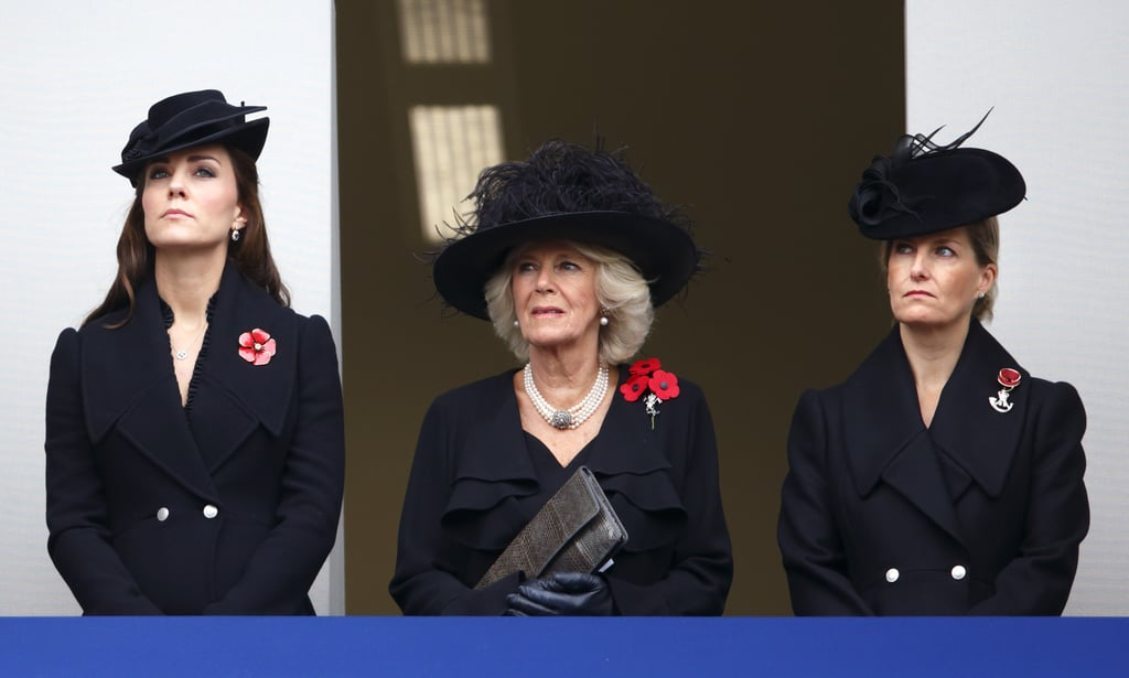 The royal family was in an appropriately solemn mood on Remembrance Sunday when they honored fallen soldiers in London. The Duchess of Cambridge stood next to Camilla, Duchess of Cornwall, as they watched Prince Charles, Prince William, and Queen Elizabeth II lay wreaths at the Cenotaph on Whitehall in London. Pregnant Kate was careful with her actions on this Remembrance Sunday after she was the subject of bizarre criticism last year when she was seen twirling her curled hair at one point during the event. This year's event was important on two accounts — it marks the 100th anniversary of the start of World War I and the 70th anniversary of the D-day invasion in Normandy, France. All eyes were also on the queen, as she had reportedly recently avoided an assassination attempt after British police allegedly arrested a group of men who were planning on attacking her during the weekend-long Remembrance Sunday events. While an assassination attempt might rattle many public figures, the queen didn't show any signs of fear and has continued on with all of her events. Meanwhile, Prince Harry made a surprise visit to Kandahar, Afghanistan, where he too partook in a poppy-wreath-laying service with British troops still stationed in that country. Their ceremony was noticeably more relaxed than the one in London, with Harry chatting with his fellow servicemen after taking part in the ceremony.