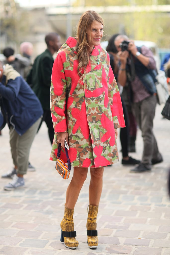 Anna Dello Russo knows how to make an entrance, this time in a camo-printed bright coat and quirky footwear.