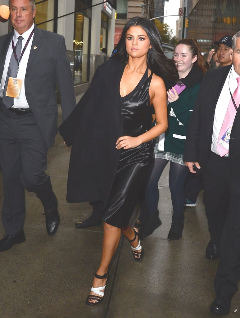 Fall staple: a black peacoat. Selena wore it with: a leather dress and strappy heels arriving at the Victoria's Secret Fashion Show in November 2015.
