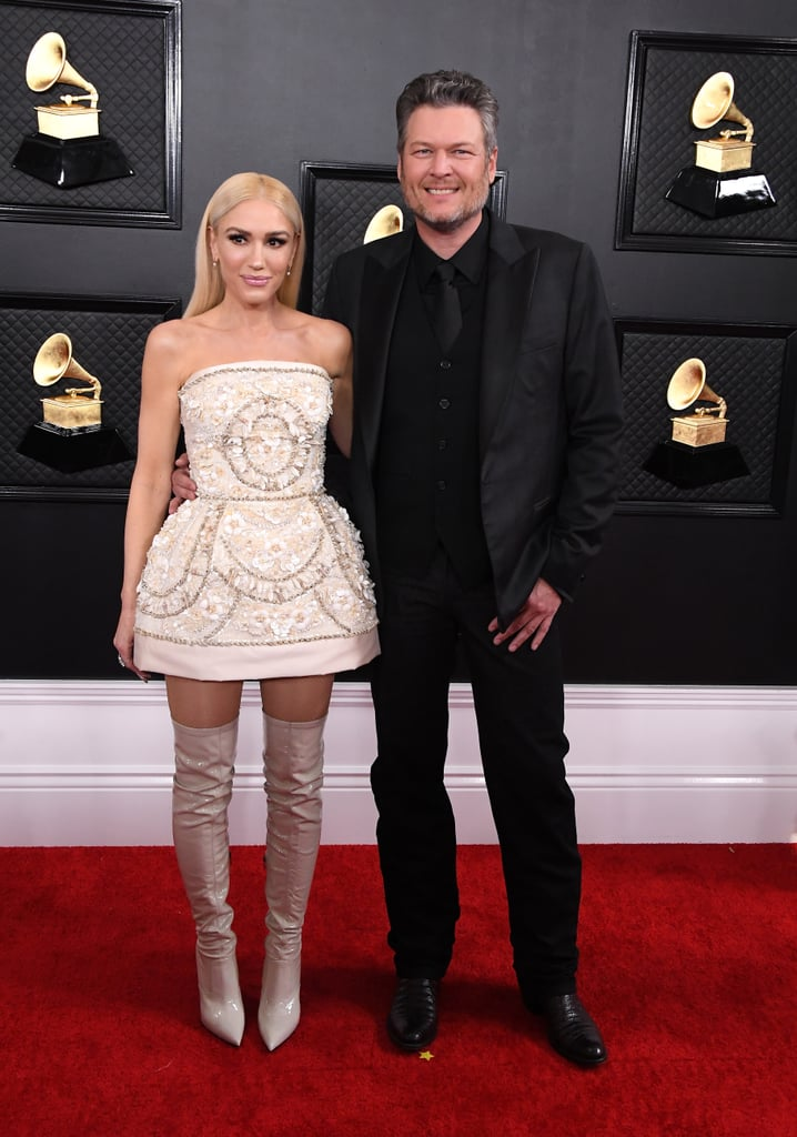 Wearing a white Dolce & Gabbana dress with boots at the 2020 Grammys.
