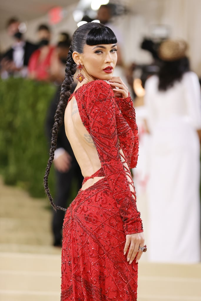 """Megan Fox's comeback year is now complete with an appearance at the Met Gala. Just one day after attending the MTV VMAs in a headline-making Mugler dress, the actress arrived at the star-studded event in an expectedly sexy Dundas gown featuring a high slit and various criss-cross cutouts. She paired the red dress with matching platform sandals, statement earrings, and a blunt bangs hairstyle.  It's not currently super clear how the outfit — created by a Norwegian designer — fits the Americana theme, but, really, is there anything more American than Megan Fox on a red carpet? """"It's on an American girl"""", Megan told Keke Palmer in a Vogue livestream interview. Browse photos of the hot look ahead. Related: Whew, These Met Gala Beauty Looks Were Worth the Wait"""