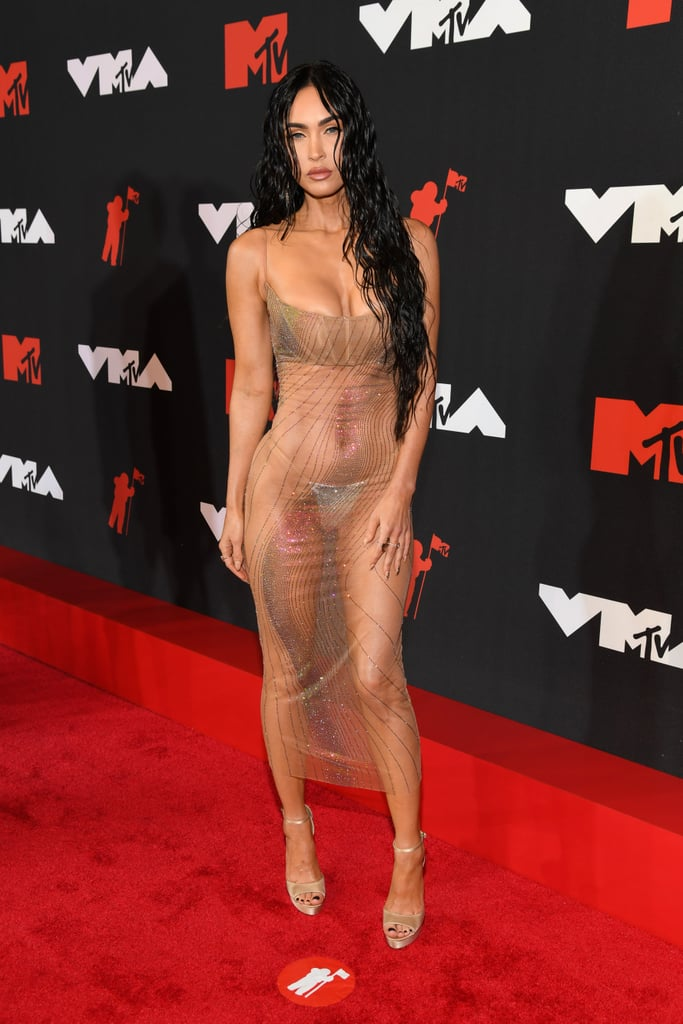 Megan Fox has had her fair share of sexy red carpet dresses, but her look at the 2021 MTV VMAs takes the cake. With boyfriend Machine Gun Kelly by her side, the actress wore a fully sheer iridescent gown with just a sequined silver thong showing underneath. As if her barely there Mugler dress wasn't striking enough, it also came with a mesmerizing glitter pattern. Styled by Megan's stylist Maeve Reilly, she topped off the sexy look with matching Jimmy Choo platforms. The actress's red carpet moment is reminiscent of another iconic Mugler look: Kim Kardashian's famous skintight nude dress at the 2019 Met Gala. Between the wet hair and similar silhouette, Megan is giving us major Kim vibes at Sunday's VMAs. Get a closer view at the actress's sexy outfit ahead.      Related:                                                                                                           If Megan Fox's Cutout Mugler Dress Looks Familiar, It's Because Kim K Wore It in 2019