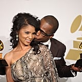 Kirk Franklin holds his Grammys while kissing wife Tammy Franklin in the press room.