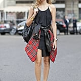 An LBD gets styled up with a funky hat and a plaid shirt tied around the waist.