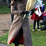 In 2014, the Duchess wore Moloh's Turpin coat, which featured scarlet interior lining. Kate wore tights and a Betty Boop Lock & Co. hat. She tucked a Really Wild Clothing printed scarf under her outerwear and accessorised with Imogen gloves, Catherine Zoraida gold earrings, and suede Emmy pumps.