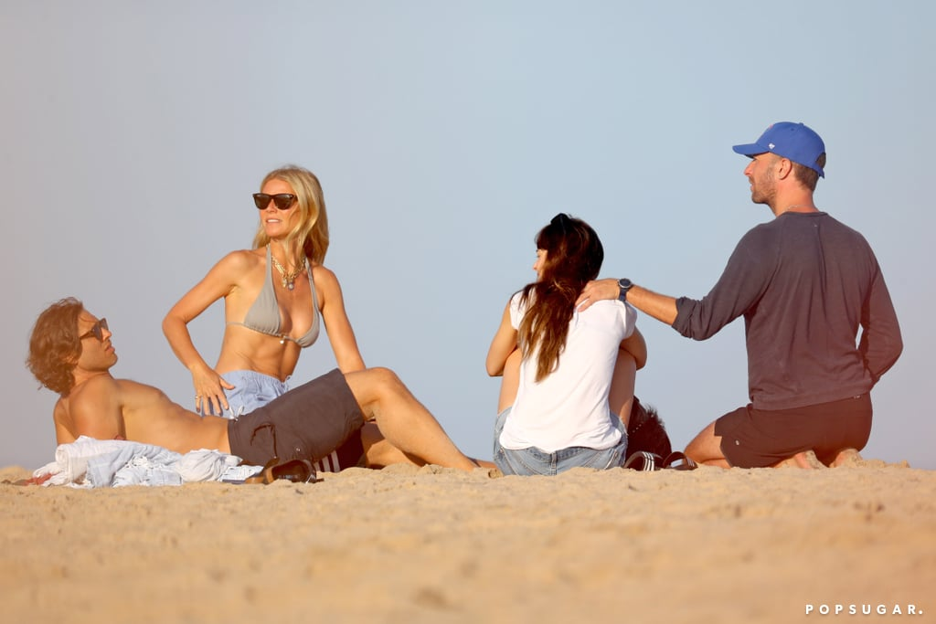 """It's a family affair! On Monday, Gwyneth Paltrow and husband Brad Falchuk were spotted on a double date with Gwyneth's ex, Chris Martin, and his girlfriend Dakota Johnson in the Hamptons. The foursome appeared to be in good spirits as they kicked back and relaxed on the beach. Gwyneth and Brad put on an affectionate display as they kissed on the sand, while Dakota and Chris also did the same and went for a sweet stroll.  The fun Summer outing comes amid Chris and Dakota's recent reconciliation. The couple first started dating back in December 2017, but they briefly split back in June. According to Us Weekly, Gwyneth was actually the one who brought them back together. """"Gwyneth is the one who pushed them to do it,"""" a source told the outlet. """"Gwyneth is happy if Chris is happy. She only wants the best for him."""" Gwyneth and Chris were married from 2003 to 2016 and are parents to 15-year-old daughter Apple and 13-year-old son Moses. In September 2018, Gwyneth made things official with Brad and they tied the knot in a star-studded ceremony at their home in the Hamptons. What a beautiful, blended family!      Related:                                                                                                           Celebrities Who Prove You Can Be Friends With an Ex"""