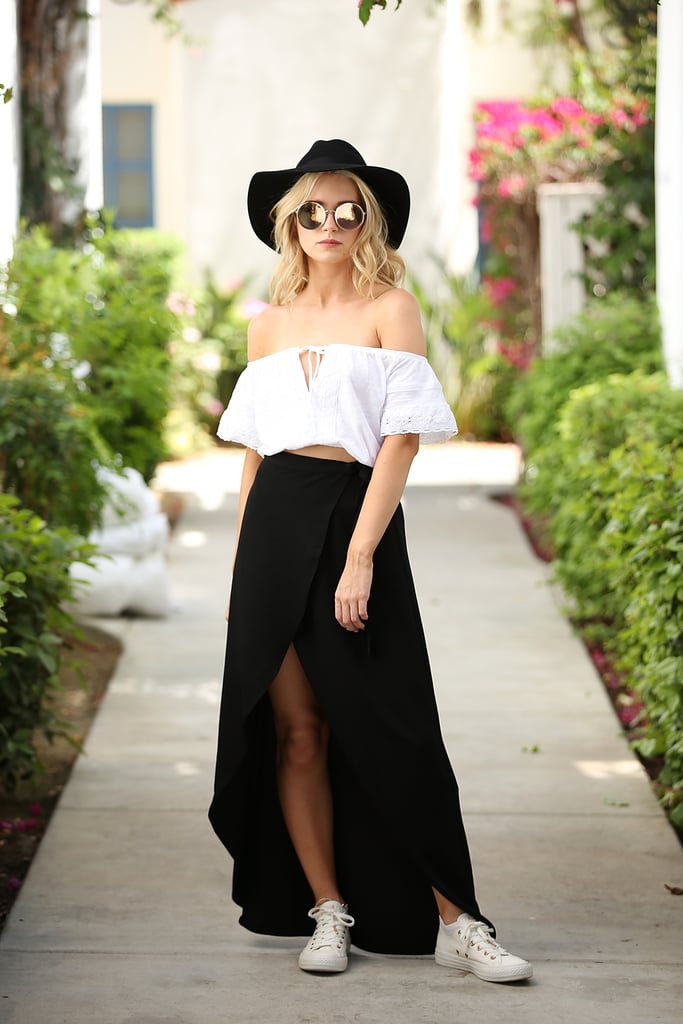 Lottie Moss wearing an off-the-shoulder crop top, slit skirt, wide brim hat, and sneakers at the festival.