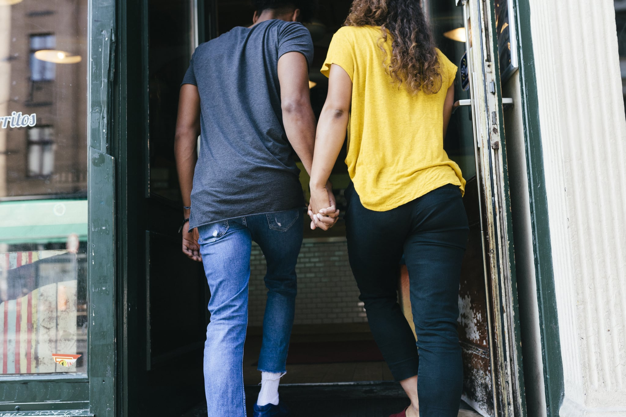 A couple holding hands and entering a restaurant together.