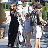 David Beckham held Harper Beckham while Victoria Beckham walked beside them around Disneyland.