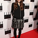 Elizabeth Olsen covered up in a floral metallic Christopher Kane dress, a leather-sleeved jacket, black tights, and black booties.