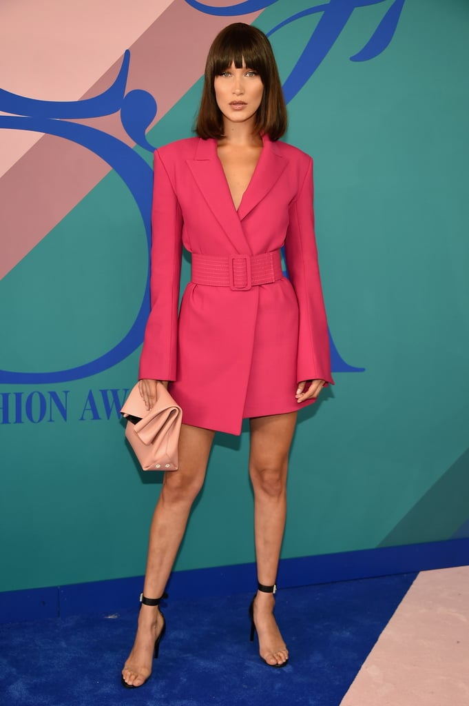 While Gigi Hadid went the minimalist route at the 2017 CFDA Awards in The Row, sister Bella chose a statement dress for the red carpet. The magenta number by Off-White featured structured padded shoulders and a retro-style wide belt that cinched in the model's waist. The bold look was very '80s, and Bella even changed up her hair with bangs and a blunt cut. See her blazer-like minidress ahead.