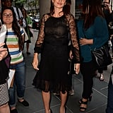 Wearing a lace-detailed black dress and matching pumps.